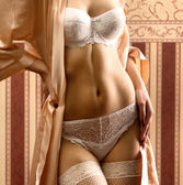 Body of young beautiful woman in lingerie standing over vintage background — Stok fotoğraf