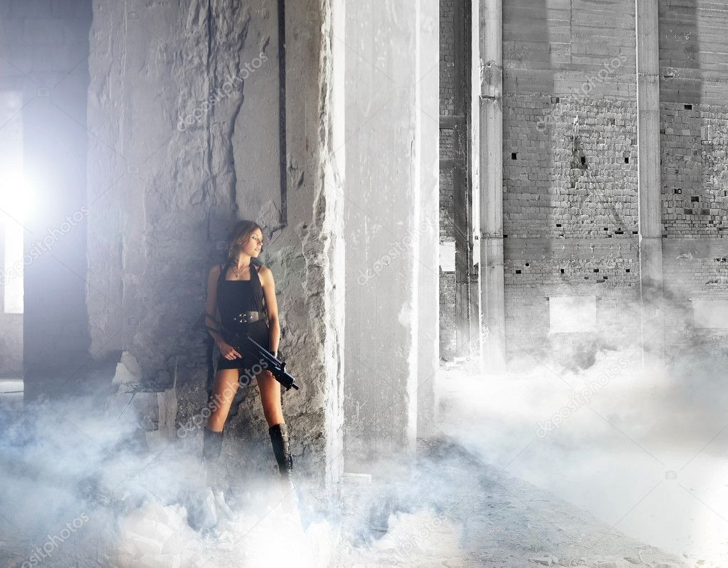 Young and sexy woman with the machine gun in apocalyptic landscape — Stock Photo #14934217