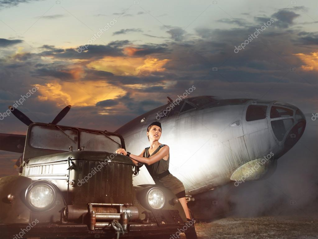 Young attractive female soldier with the plane and car — Stock Photo #14934557