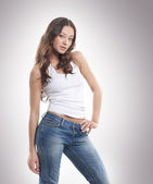 Stock photo of young, fit and sexy woman in jeans and white top — Stock Photo