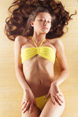 Young sexy brunette in yellow swimsuit — Stock Photo