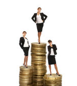 Young attractive businessladies on coin towers — Stock Photo