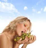 Young beautiful woman eating grapes — Stock Photo