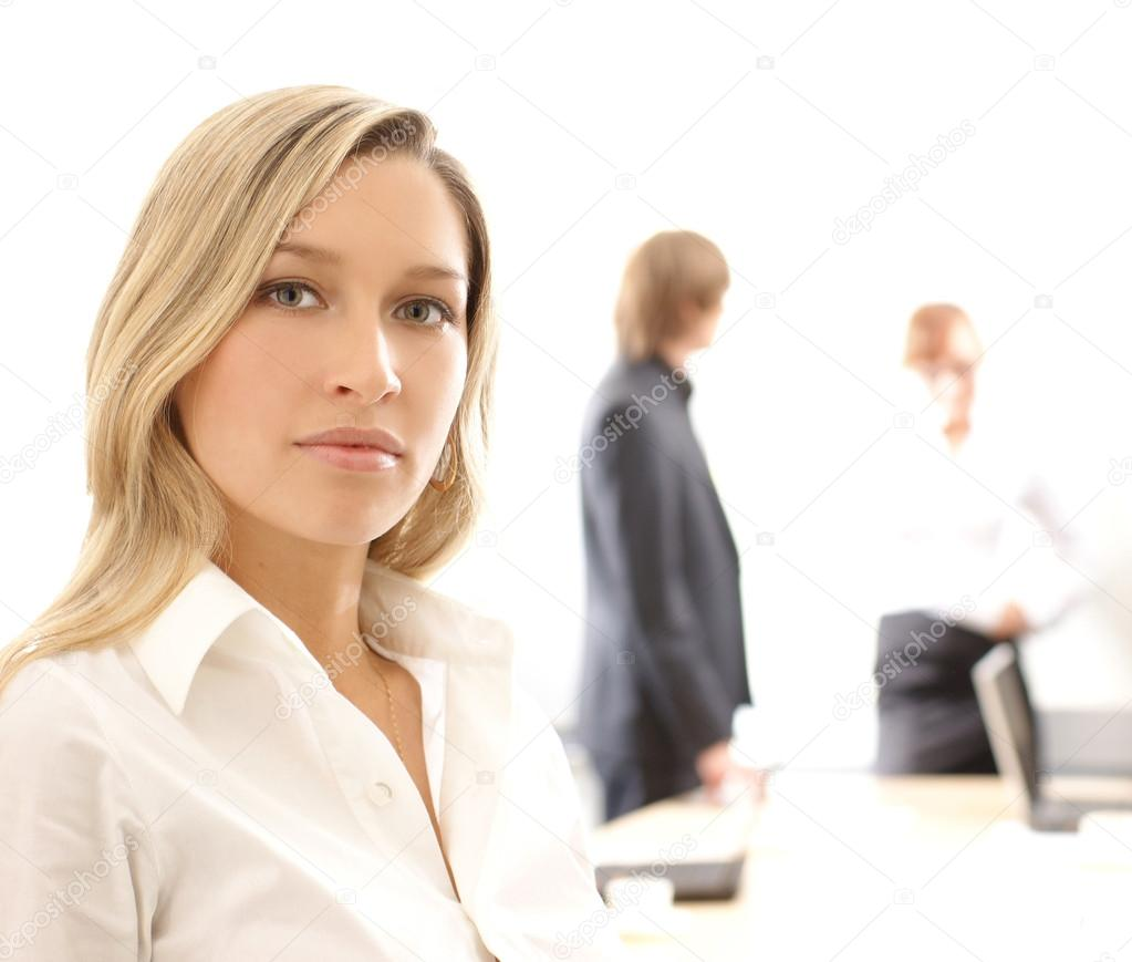 Young business woman in front, the rest of the business team on the background. Image isolated on white. — Stock Photo #14978283