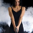 Sexy woman with weapon on smoky background — Stock Photo