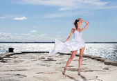 Young sexy girl in a white dress standing on a pier — Stock Photo