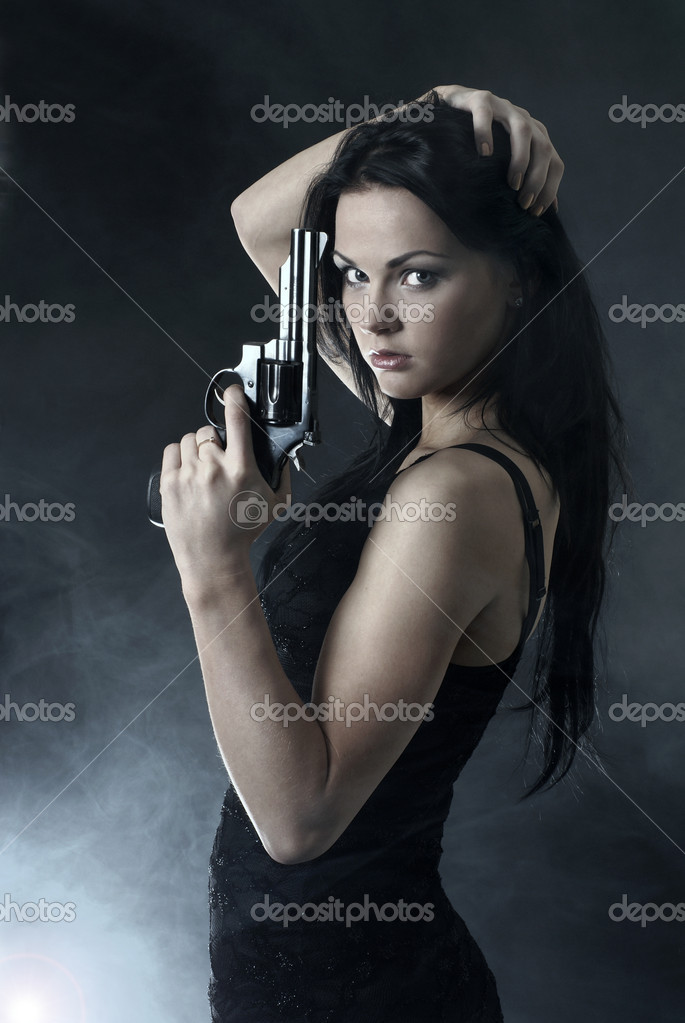 Sexy woman with weapon on smoky background — Stock Photo #14989935