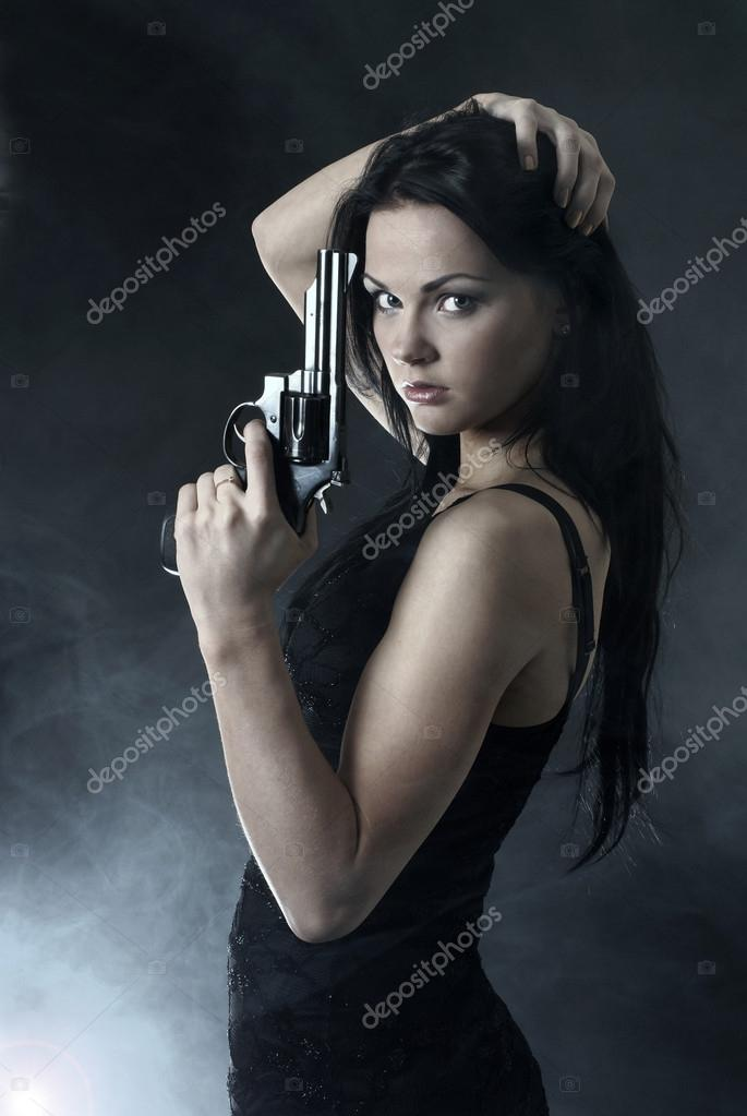 Sexy woman with weapon on smoky background — Stockfoto #14989935