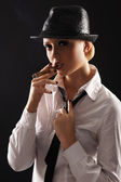 Young attractive female gangster smoking cigar over dark background — Stock Photo
