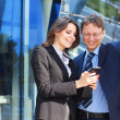 Foto Stock: Businessmshowing something in smartphone to his female assistant
