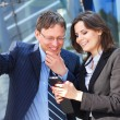 Businessman showing something in the smartphone to his female assistant — Stock Photo #15382331