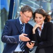 Businessman showing something in the smartphone to his female assistant - Stock Photo