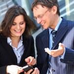 実業家は彼の女性アシスタントをスマート フォンで何かを示す — ストック写真