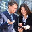 Stock Photo: Businessman showing something in the smartphone to his female assistant