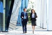 Negócios andando e falando no meio do rua — Foto Stock