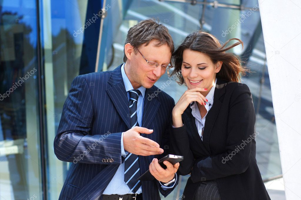Conceptual photo of businessman showing something in the smartphone to his female assistant — Stock Photo #15382349