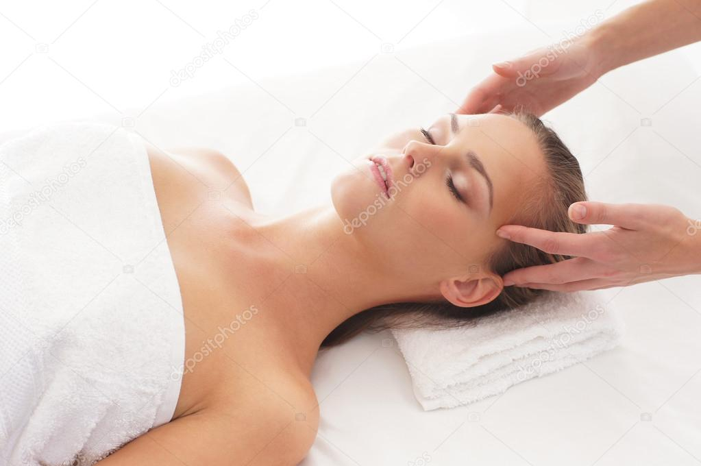 Young attractive woman getting massaging treatment over white background — Lizenzfreies Foto #15384409