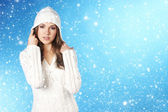 Young pretty woman in winter dress over blue background with som — Stock Photo