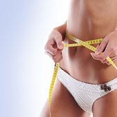 Young attractive woman measures her body — Stock Photo