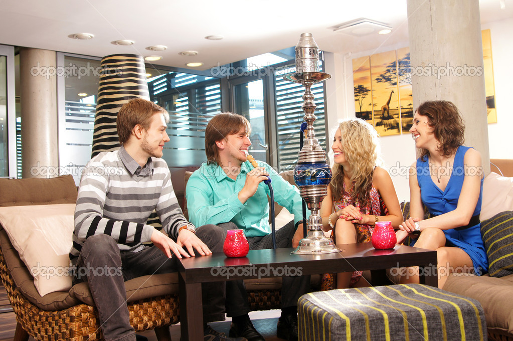 Group of young and sexy smoking hookah in the lounge caffee — Stock Photo #15393269