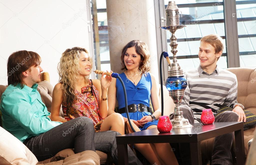 Group of young and sexy smoking hookah in the lounge caffee — Stock Photo #15393597