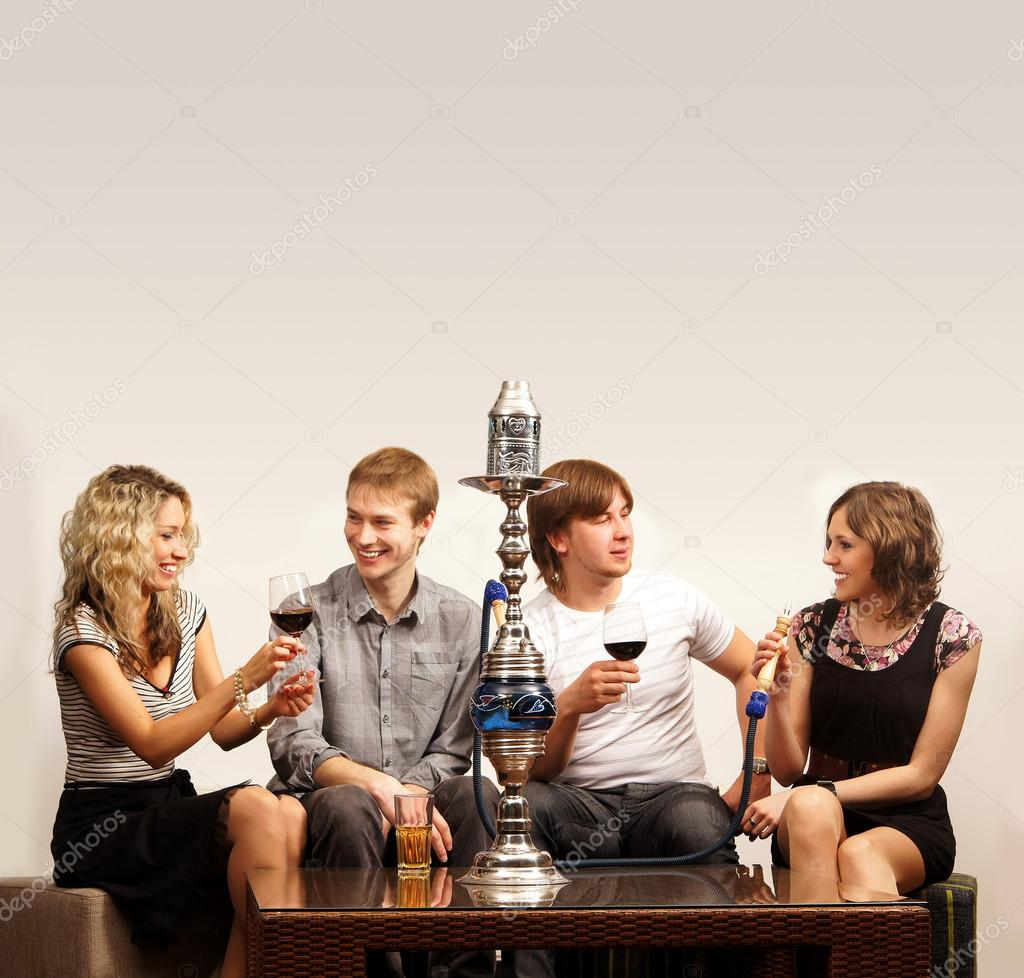 Group of young and sexy smoking hookah in the lounge caffee — Zdjęcie stockowe #15395357