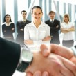 Group of business over futuristic background with a blury handshae in front — Stock Photo #15402943