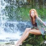 Young and beautiful girl in bikini taking bath in a waterfall — Stock Photo