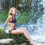 mladá a krásná dívka v bikinách přijetí koupele v vodopád — Stock fotografie