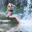 Stock Photo: Young and beautiful girl in bikini taking bath in a waterfall