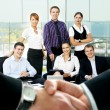 Group of business over futuristic background with a blury handshae in front — Stock Photo