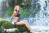 Young and beautiful girl in bikini taking bath in a waterfall — Stock Photo