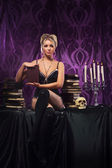 Young attractive woman in sexy lingerie posing in gothic interior — Stock Photo