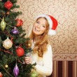 Beautiful teenager girl decorating the Christmas tree — Stock Photo #15447457