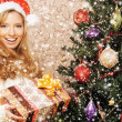 Stock Photo: Beautiful teenager girl with the present near the Christmas tree