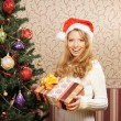 Beautiful teenager girl with the present near the Christmas tree — Stock Photo