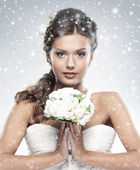 Young attractive bride with the bouquet of white roses — Stock Photo