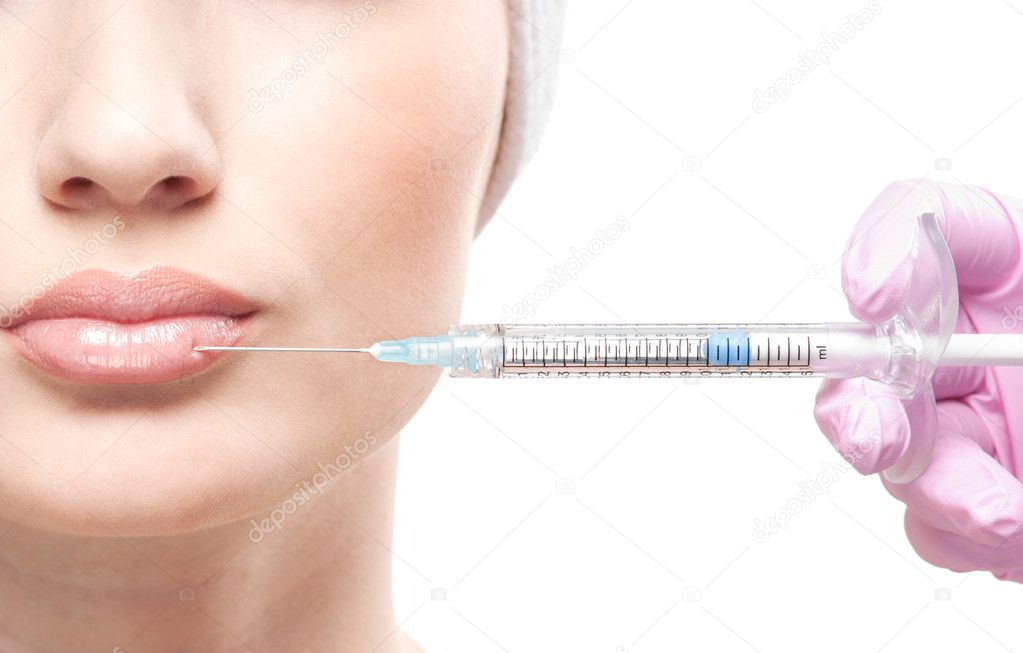 Beautiful woman gets an injection in her face isolated on white — Stock Photo #15442691