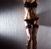 Young sexy woman in erotic lingerie standing near the grey wall — Stock Photo