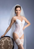 Young sexy bride in erotic lingerie over blue — Stock Photo