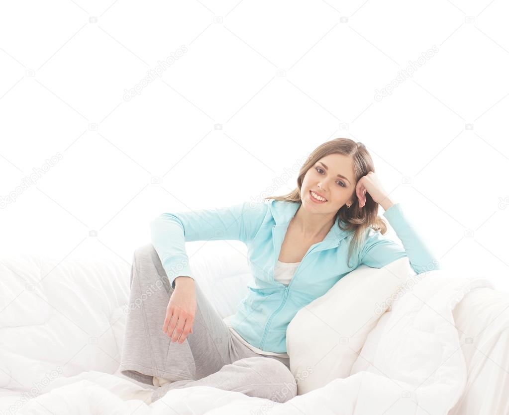 Young, attractive, happy woman sitting in the bed over white background — Stock Photo #15522927