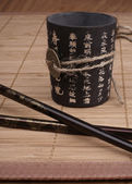 Japanese bowl with chopsticks over dark background — Stock Photo