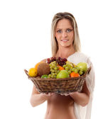 Attractive woman with a basket full of fruits — Stock Photo