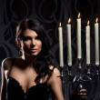 Fashion shoot of young sexy woman with a candles — Stock Photo