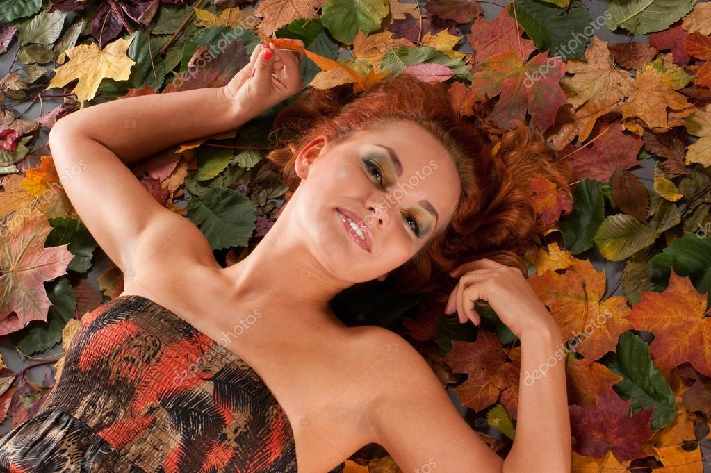 Attractive redhead in autumn leaves — Stock Photo #15866909