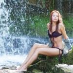 Young and beautiful girl in bikini taking bath in a waterfall — Stock Photo #15870495