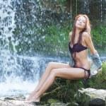 Young and beautiful girl in bikini taking bath in a waterfall — Stock Photo #15870499