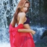 Young and beautiful girl in bikini taking bath in a waterfall — Stock Photo #15870515