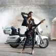 Sexy female biker with a guitar - Stok fotoğraf