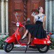 Foto Stock: Young attractive girl with scooter